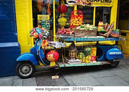 Blue motorbike display with fruits, vegetables, lampoons, buddha head in front of Chinese shop, Chinese Full Moon festival, Dublin, Ireland, 26 August 2017