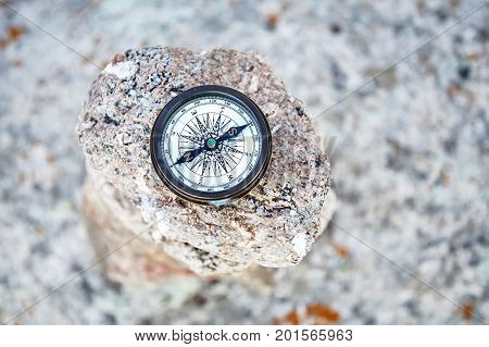 Round Vintage Compass on the stone background. Travel and adventure concept.