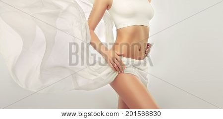 Perfect slim toned young body of the girl . An example of sports , fitness or plastic surgery and aesthetic cosmetology. Healthy Breast .