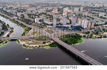 Residential district in a large metropolis with road junctions and houses near Dnepr river in Kiev, Ukraine. Aerial view. From above.