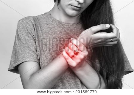 Woman holding sore wrist in her hand over gray background black and white with red accent