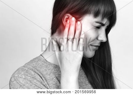 Young woman has a sore ear. girl suffering from otitis closeup over gray background. Black and white with red accent