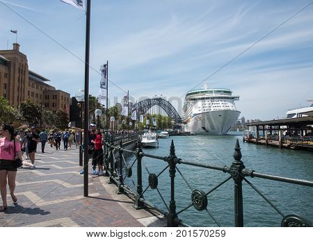 SYDNEY,NSW,AUSTRALIA-NOVEMBER 20,2016: Crowds on the Circular Quay waterfront with overseas passenger terminal with cruise ship, Harbour Bridge and Museum of Contemporary Art in Sydney, Australia