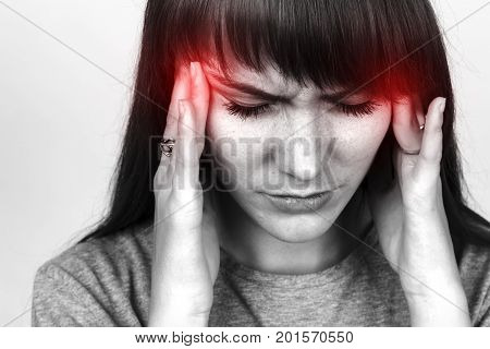 Portrait of a pretty woman over gray background stress and headache having migraine pain black and white with red accent