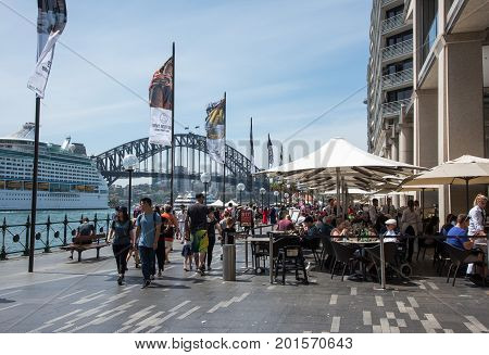 SYDNEY,NSW,AUSTRALIA-NOVEMBER 20,2016: Tourists walking and at sidewalk cafe at the Circular Quay development with cruise ship and Harbour Bridge views in Sydney, Australia
