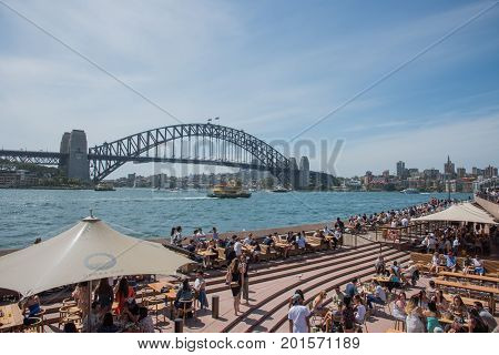 SYDNEY,NSW,AUSTRALIA-NOVEMBER 20,2016: Tourists at the Opera Bar on the Parramatta River waterfront with Sydney Harbour Bridge View in Sydney, Australia