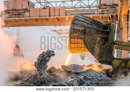Pouring the hot melt slag by truck transporter to slag dump. Heavy industry. Part of the process in metallurgy.