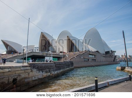 SYDNEY,NSW,AUSTRALIA-NOVEMBER 20,2016: Sydney Opera House, sandstone boundary wall and tourists in Sydney, Australia.