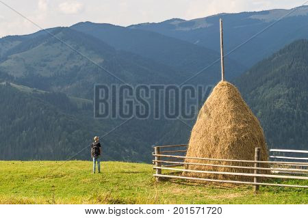 Trekking male hiker standing near haymow on top of carpathian hills and enjoying beautiful sights. Sight of beautiful west ukrainian mountain area in summer at sunset
