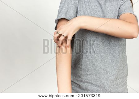 Girl in grey shirt scratching her arm. Scabies. Scratch the hand over gray background