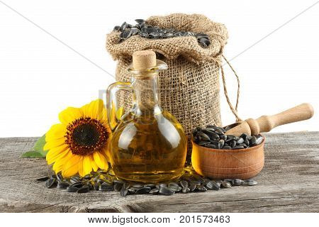 Sunflower oil in glass jug , seeds and flower on old wooden table with white background