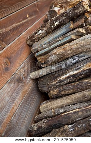 Wooden logs againt a woodcutter hut in the woods