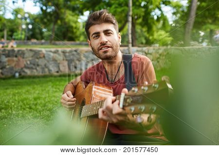 Talented attractive male musician looking at camera playing guitar in the park, having good time sitting on grass enjoying splendid weather. Bearded musician singing songs outdoors.