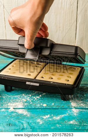 Making waffles at home - batter in waffle iron. Cooking background.
