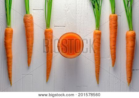 Healthy carrot juie in a jar with carrots on white wooden table top view. Healthy food background concept