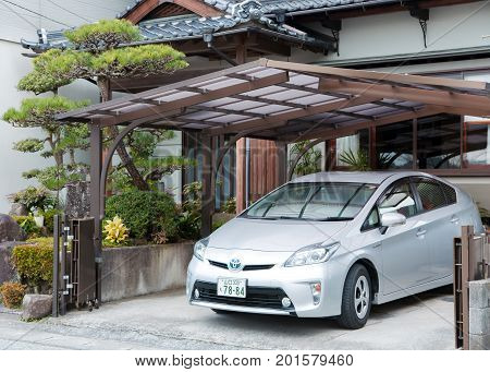 JAPAN, IWAKUNI, APRIL, 04, 2017 - Private Toyota Prius parked near the house under a small canopy in Iwakuni, Japan