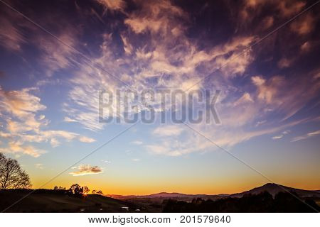 Bright sunrise in sky over New Zealand landscape