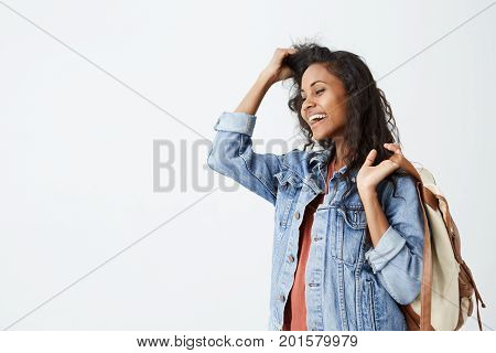 Portrait of beautiful young dark-skinned female with wavy dark hair wearing casual red T-shirt and denim jacket with backpack on her shoulder smiling pleasantly. Trendy hipster woman having good mood while posing.