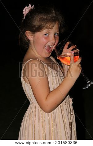 4TH AUGUST 2017,TURKEY: An unknown young girl pretending to drink a glass of wine at a wedding in turkey, 4th august 2017