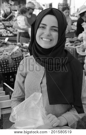 CALIS, TURKEY - 6TH AUGUST, 2017:A portrait of a young turkish girl working at a fresh fruit and vegetable produce market in Calis, Turkey, 6th august 2017