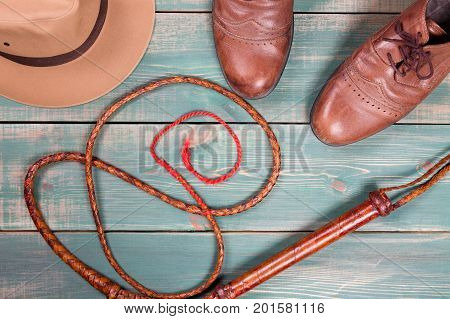 Travel and adventure concept. Vintage fedora hat bullwhip and old brown shoes on green wooden table. Top view
