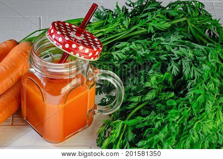Carrot juice in a jar with a red lid in a white polka dots and an orange straw and carrots on white wooden table top view. Healthy food background concept