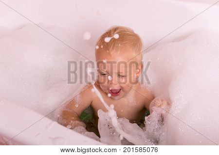 Playful Toddler Splashing In A Bath. Funny Baby Boy Playing Whit Soapy Water.