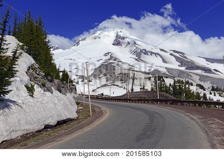 Snow covered Mount Hood, a volcano in the Cascade Mountains in Oregon popular for hiking, climbing, snowboarding and skiing, despite the risks of avalanche, crevasses and volatile weather on the peak. poster
