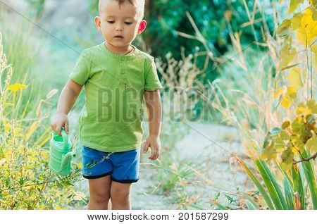 The Little Boy In The Village With A Watering Can Sprinkler
