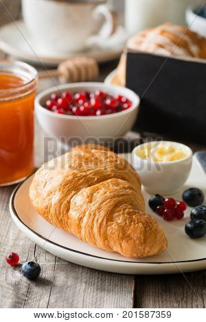 Continental breakfast with croissant, butter, jam, coffee and fruits. Closeup view, selective focus. Empty black chalkboard copy space for text