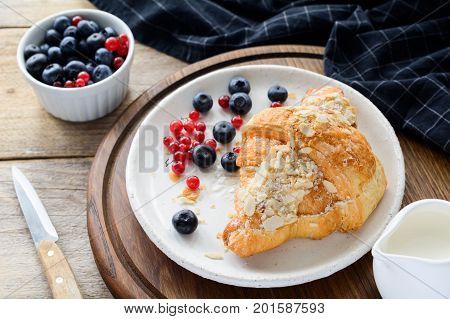 Fresh croissant, blueberries and red currants on white plate. Continental breakfast
