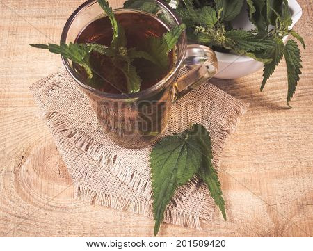 Healing Tea With Nettle. Tea In A Glass Cup On A Wooden Table. The Source Of Vitamins.