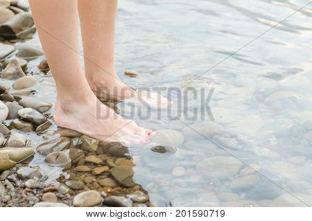 Female Feet On Pebbles In The Water.