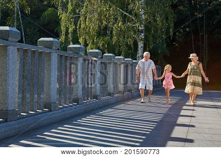 Girl with grandfather and grandmother. Family walking, summer day. Strolling through the park.