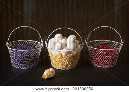 Three baskets and one is filled with eggs but one egg has fallen out and has broken.