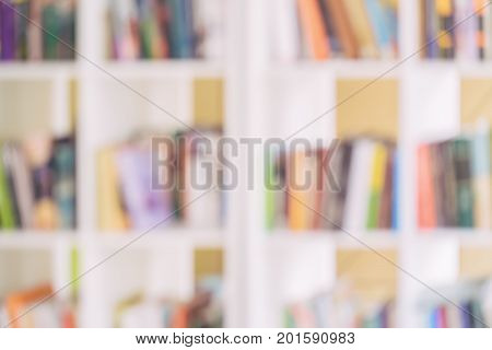 Abstract blurred white bookshelves with books, manuals and textbooks on bookshelves in library or in book store, for backdrop. Concept for education, literature