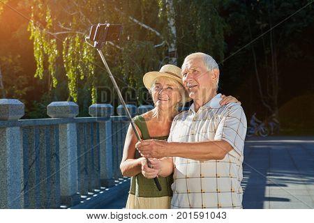 Old couple taking selfie outdoors. Senior male holding monopod. Technology use among seniors.