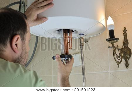 Man putting a new water heater in a boiler