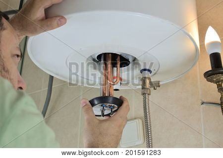 Man's hand putting a new water heater in a boiler
