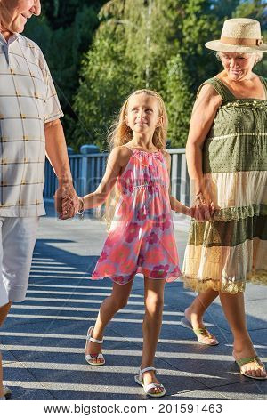 Grandchild and grandparents holding hands. People walking outdoors, summer day. Raising the future.