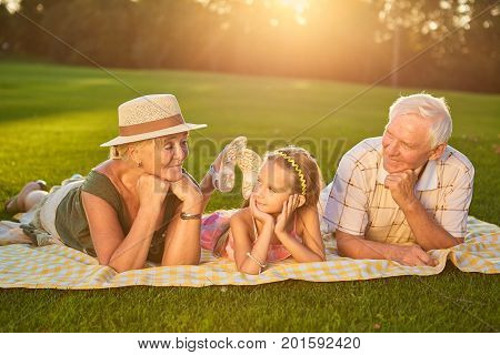 Grandparents with grandchild lying outdoors. Girl looking at her grandmother.