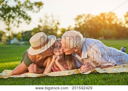 Grandparents kissing granddauther. People lying outdoors. Love to grandchildren.