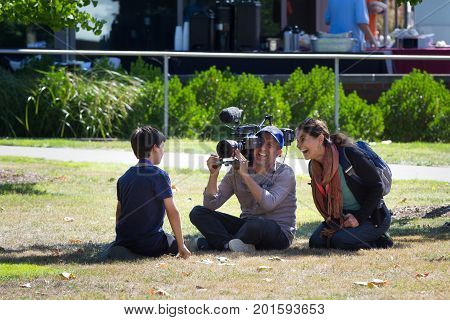 SALEM, WASHINGTON, USA - AUGUST 21, 2017: PBS Nova team interviews a boy on the lawn of Willamette University after solar eclipse.
