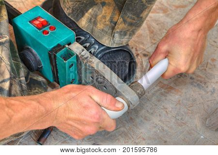 Plumber installing pipes in home ppr plastic pipe hot melt welding machine close-up.