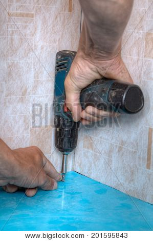 The laborer screws the fastening screw into the plastic panel using a cordless electric screwdriver hands working closeup.