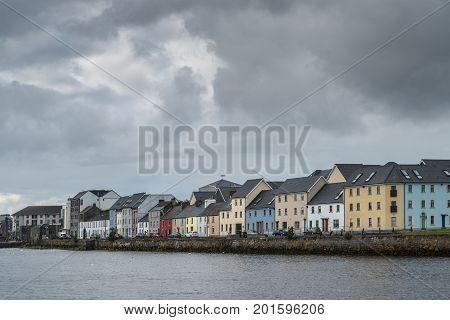 Galway Ireland - August 3 2017: Closeup of part of The Long Walk Quay of the old port seen from across the dark Corrib River mouth. All under heavy storm sky. The different paint colors of the houses shine.