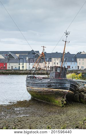 Galway Ireland - August 3 2017: The wreck of an old fishing vessel leans against dock wall and stands on dry shore in old Claddagh Port. Colorful houses of The Long Walk Quay form background. Light gray sky.