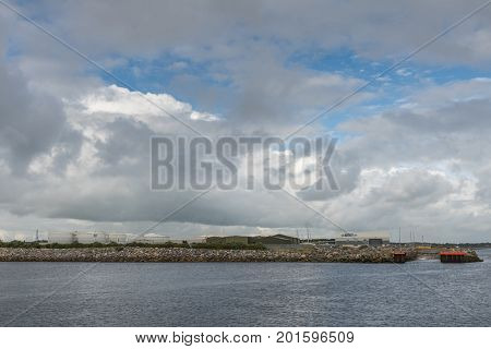 Galway Ireland - August 3 2017: Enormous cloudscape with blue patches above the new commercial harbor with battery of large white fuel tanks slipway and warehouses. Shot from across Corrib River.