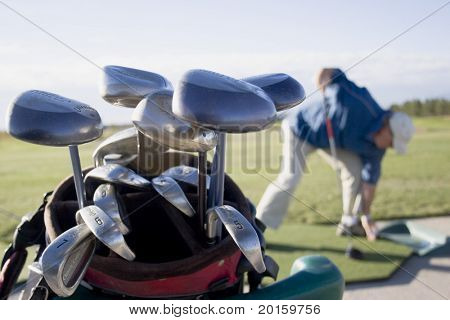 golf clubs with senior golfer in background
