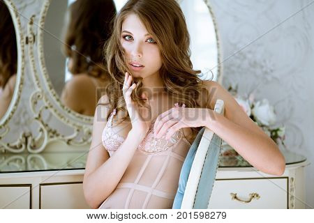 Fashionable female portrait of cute lady in pink bra indoors. Close up beautiful sexy model girl in elegant pose. Closeup beauty blonde woman with hairstyle and makeup. Glamorous face with make up